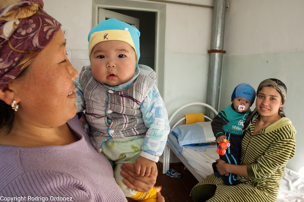 7-month-old Ariet (left) and Abdusamad, 1, pose for a photograph with their mothers Mirgul and Nilufar at Children's State Hospital in Osh, Kyrgyzstan. Save the Children is providing this hospital with medicines and medical equipment to treat anemia and respiratory infections such as pneumonia, which are common among pregnant women, mothers and children.