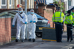 © Licensed to London News Pictures. 12/11/2020. Reading, UK. Forensic investigators walk towards a property where the a man died in the early hours of Thursday. Thames Valley Police is investigating the unexplained  death of a man in Reading. At approximately 04:55GMT South Central Ambulance Service called police officers to a house on Oxford Road, Reading. On attendance they found that a man in his fifties had died. A 44-year-old man, a 38-year-old man and a 43-year-old man all from Reading have been arrested on suspicion of murder. Photo credit: Peter Manning/LNP