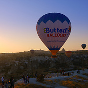 Hot air balloons fly in the morning and tourists enjoying the view in Cappadocia, Turkey