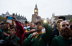 © London News Pictures. 24/10/2015. London, UK. Fans gather in Parliament square as member soft the 1995 South African Rugby World Cup winning team take part in an early morning, 2 mile run around westminster to mark the anniversary of in the 1995 winning team going for a morning jog. The event takes place on the morning of the Rugby World Cup semi-final between South Africa and New Zealand. Photo credit: Ben Cawthra /LNP