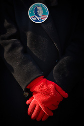 Lady with red gloves and Barack Obama button watching inauguration of Barack Obama from front steps of Lincoln Memorial, Washington D.C., USA.