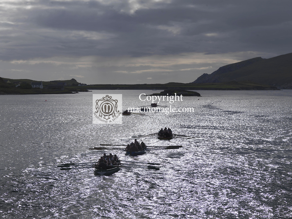 The Seine Boat Race heads into the setting sun near the finish line at Portmagee regatta in County Kerry, Ireland<br /> Picture by Don MacMonagle