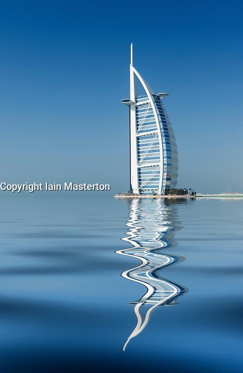 Luxury Burj al Arab Hotel reflected in the sea in Dubai United Arab Emirates UAE