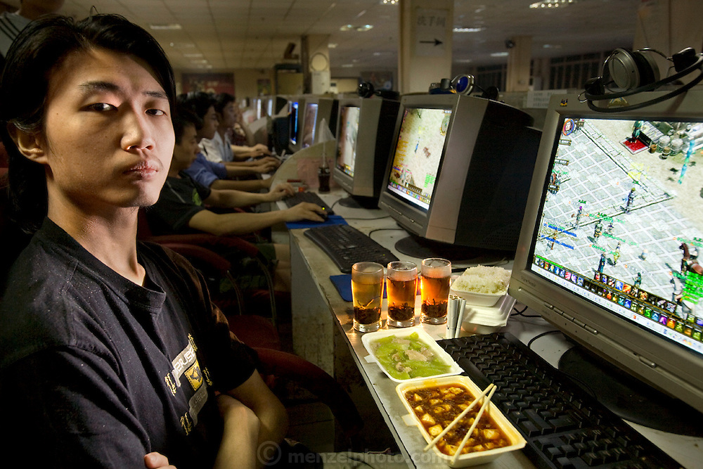 Xu Zhipeng, a freelance computer graphics artist and Internet gamer, with his typical day's worth of food in his rented chair at the Ming Wang Internet Café in Shanghai, China. (From the book What I Eat: Around the World in 80 Diets.) The caloric value of his day's worth of food in June was 1600 kcals. He is 23 years of age; 6 feet, 2 inches and 157 pounds.  He lives at his computer station, day and night, sleeping there when he's tired and showering once a week at a friend's apartment. His longest continuous game lasted three days and nights. When he tires of gaming at the café he reads fantasy books. ?It's nice to rest your eyes on a book,? he says, even though he's reading it online. China has more than 300 million Internet users?a number close to the entire population of the United States.