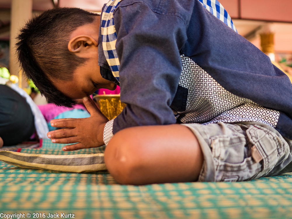 19 JUNE 2016 - DON KHONE, CHAMPASAK, LAOS: A boy prays in a Buddhist temple in Don Khone village on Don Khone Island. Don Khone Island, one of the larger islands in the 4,000 Islands chain on the Mekong River in southern Laos. The island has become a backpacker hot spot, there are lots of guest houses and small restaurants on the north end of the island.    PHOTO BY JACK KURTZ