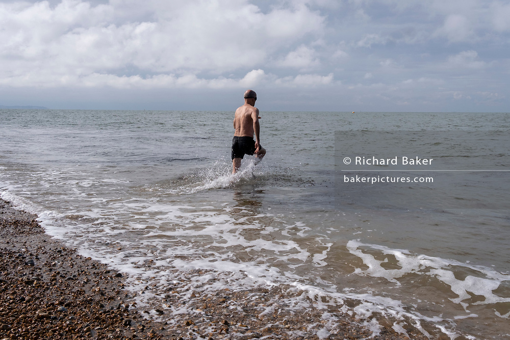 A sea swimmer runs into cold tidal waters of the Thames Estuary, on 25th July 2021, in Whitstable, England.