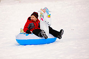 02 JANUARY 2021 - DES MOINES, IOWA: A child riding an inflatable pool toy slides down the hill below the Iowa Supreme Court. The hill is one of the most popular spots in Des Moines for sledding and winter play. Hundreds of people took advantage the warmer weather and the week's record snow to spend time on the slopes around the Supreme Court and neighboring capitol. The high temperature Saturday was about 25F (-4C).     PHOTO BY JACK KURTZ