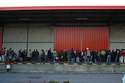 Refugees line up for their evening meal outside a disused warehouse in Calais, France. The charity Secour Cathlique helped provide two meals a day and some clothes for the refugees. .After the Sangatte refugee camp closed down an average of 200 refugees lived on the streets of Calais, without food, money or accommodation, trying most nights to get to Britain.  There were many different nationalities, mainly Iraqi and Afghani, but also Sudanese, Palestinian and Turkish. 95% are male, aged between 16 and 50.
