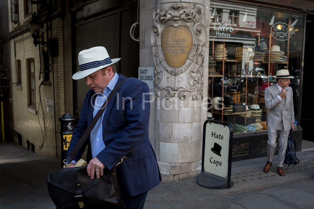 A gentleman wearing a Trilby hat searches his shoulder bag while walking past Laird Hatters where another man stands in a Panama, on the Strand, on 5th July 2017, in central London, England.
