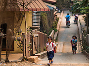 11 MARCH 2016 - LUANG PRABANG, LAOS:  Children cross a bridge over a stream in the community of Chomphet, across the Mekong River from Luang Prabang. Laos is one of the poorest countries in Southeast Asia. Tourism and hydroelectric dams along the rivers that run through the country are driving the legal economy.      PHOTO BY JACK KURTZ