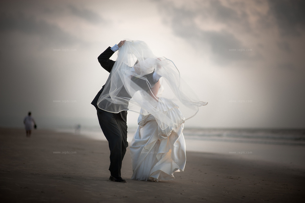 The bridegroom tries to hold on to the bride's veil during a fun couple shoot on the beach, after their Catholic wedding in Goa.