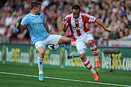 Stoke's Matthew Etherington ® battles with Manchester City's James Milner during the Barclays Premier league match, Stoke city v Manchester city at the Britannia Stadium in Stoke on Trent on Sat 14th Sept 2013. pic by Jeff Thomas, Andrew Orchard sports photography,