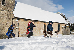 © Licensed to London News Pictures. 27/02/2018. Broomfield, UK. A family walk past St Margaret's Churn in Broomfield, Kent after sledging on a nearby hill. Freezing temperatures and heavy snow are affecting large parts of Kent.  Photo credit: Peter Macdiarmid/LNP