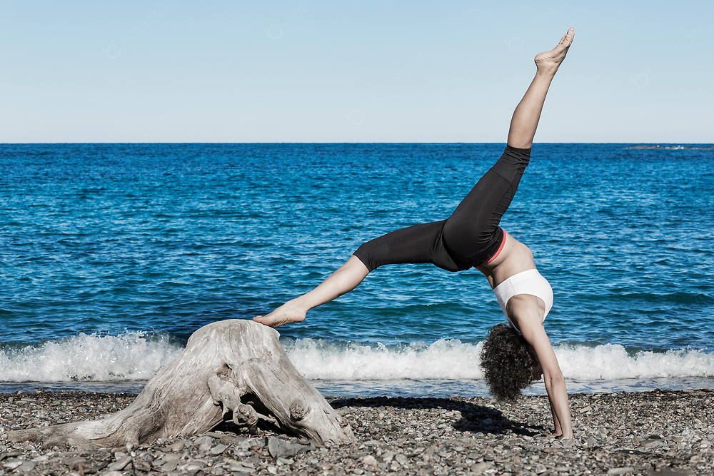 Woman doing yoga exercises at the beach