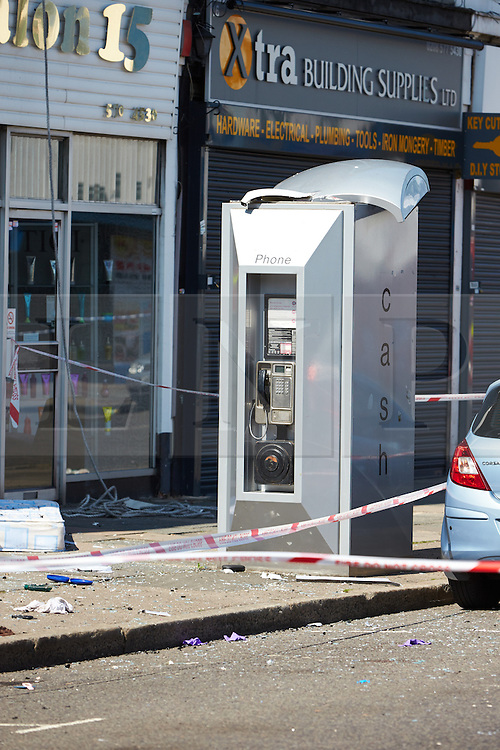 © Licensed to London News Pictures.  10/07/2013. LONDON, UK. A phone box, with a damaged roof. The damage is believed to be from a person jumping from a second storey window attempting to escape a fire in flat above a shop on New Heston Road (Church Road), Hounslow. Two men and a woman jumped from the building before fire crews arrived. The woman, thought to be 30 years old, died at the scene and another body was discovered inside. Photo credit: Cliff Hide/LNP