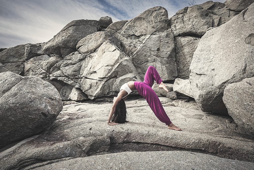Young woman doing a back bending yoga pose outdoors