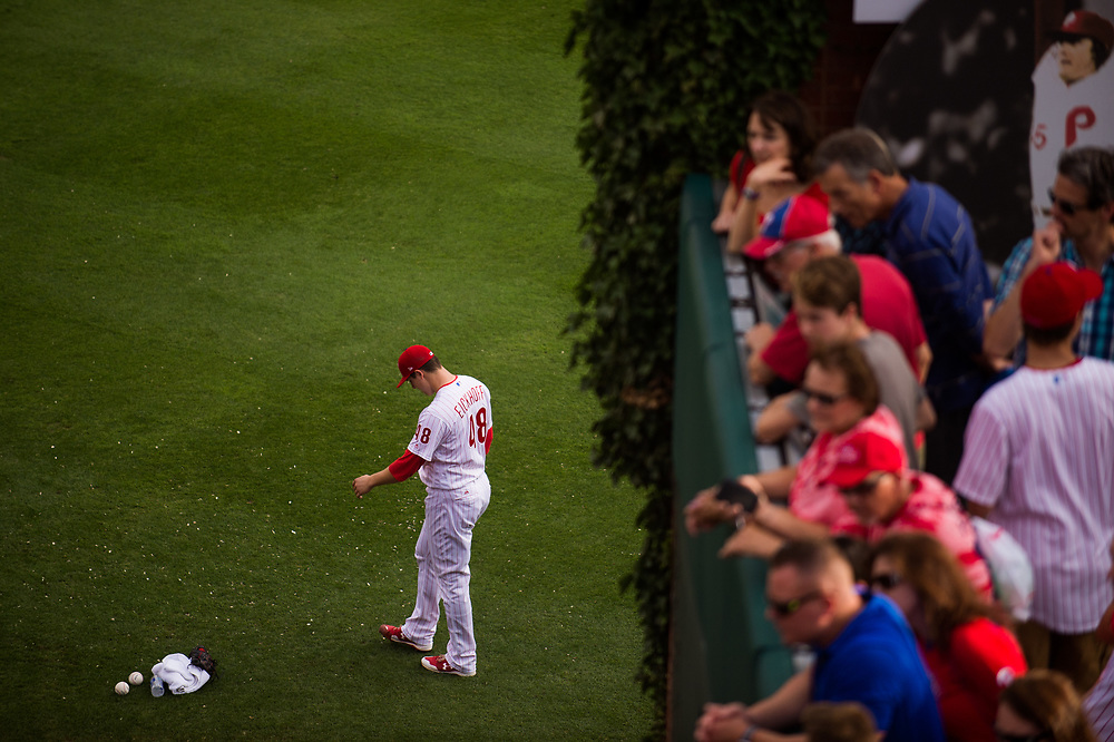 Fans watch Phillies starting pitcher Jerad Eickhoff warm up in the outfield before facing the Braves