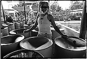 Blind drummer practicing on an array of pan drums for Carnival.