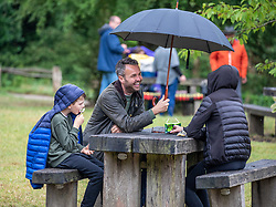 © Licensed to London News Pictures. 08/07/2020. Surrey, UK. Picnickers Matthew Allen from Surrey with his nephew and niece Bella and Ollie brave the midsummer rain on Box Hill in the Surrey Hills as weather forecasters predict a mild but wet couple of days ahead followed by sunnier and warmer weather for the weekend. Photo credit: Alex Lentati/LNP