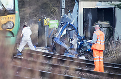© Licensed to London News Pictures. 17/02/2018. Horsham, UK. A railway worker stands near the remains of a car near a level crossing where two people have been killed near the village of Barns Green after a train hit a car. Photo credit: Peter Macdiarmid/LNP