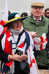 Whitehall, London, April 4th 2015. As PEGIDA UK holds a poorly attended rally on Whitehall, scores of police are called in to contain counter protesters from various London anti-fascist movements. PICTURED: A PEGIDA supporter sticks his tongue out at the camera as a woman stares mistrustfully  into the lens