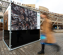 Edinburgh, Scotland, UK. 20 March, 2019. The  opening of a major outdoor photography exhibition highlighting the impact humans have on the natural world, called  A Human Touch, in front of the Scottish Parliament as part of Edinburgh Science Festival. Pictured, a woman walk past one of the photographs