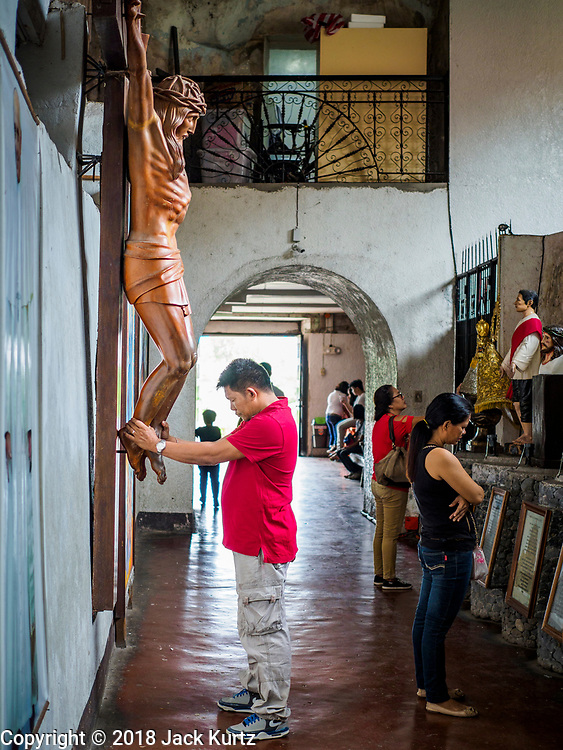 21 JANUARY 2018 - LEGAZPI, ALBAY, PHILIPPINES: AA man prays at a crucifix in Our Lady of the Gate Parish in Legazpi. The church, built in 1773, was known by its Spanish name, Parroquia Nuestra Señora de la Porteria, before the American colonization of the Philippines.     PHOTO BY JACK KURTZ