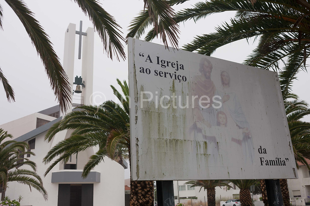 Religious lifestyle choices seen in a faded picture of Christian family morals, outside a Catholic church, on 18th July 2016, at Costa Novo, near Aveira, Portugal. Fading and suffering from green algae, the picture of the perfect family who attend Mass is seen in front of the tall cross and building exterior. There are an estimated nine million baptised Catholics in Portugal 84% of the population, in twenty dioceses, served by 2,789 priests. 19% of the national population attend mass and take the sacraments regularly.
