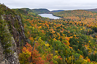 Vivid fall colors fill the valley of the Porcupine Mountains in Michigan's Upper Peninsula. This state park preserves one of the largest areas of wilderness left in the Midwest The steep cliffs known as The Escarpment rises 500 feet above the Lake of the Clouds. It is a fitting name since I never did see this lake without a cloudy sky above it. On the other side of the cliffs is Lake Superior. It can just barely be seen in between two hills at the top of the picture. This picture was taken at the beginning of a 28 mile backpacking trip into the wilderness.<br />