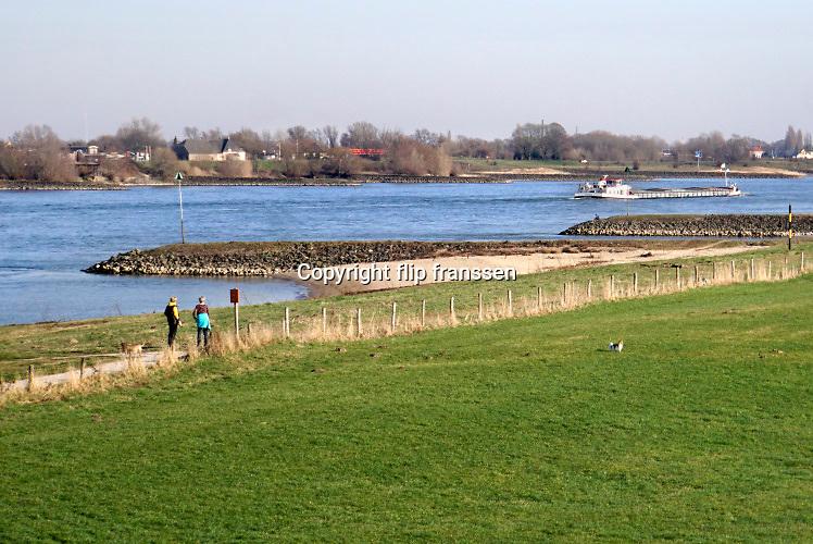 Nederland, Millingen aan de Rijn, 23-2-2019Op en langs de dijk wandelen en fietsen mensen in de zon. Het is uitzonderlijk warm en mooi weer voor de tijd van het jaar . Weerrecord in februari . De natuur staat op springen en mensen komen fietsen en wandelen in dit gebied .Foto: Flip Franssen