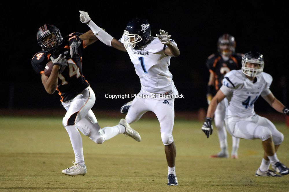 Winter Park receiver Gabriel Jenkins (14) catches a pass in front of Dr. Phillips defensive back Jalean Perkins (1) during the first half of a high school football game in Winter Park, Fla., Friday, Nov. 7, 2014.(Photo by Phelan M. Ebenhack)