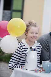 Portrait of a teenage girl holding balloons and smiling, Bavaria, Germany