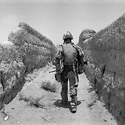 """A Canadian soldier walks up a narraow path between mud walls on what is known as """"Route Nightmare"""" in a village in Panjwaii District, Kandahar, Afghanistan. The mud walls and unpaved paths and roads due to lack of development and reconstruction in almost all of the impoverished rural areas of Kandahar allows for the easy planting of land mines and road side bombs by insurgents. (Credit Image: © Louie Palu/ZUMA Press/The Alexia Foundation).June 20, 2010.Photograph taken on film exact date estimated and not known....."""