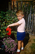 A young boy waters shrubs with a red toy watering can in the family garden on an Essex estate in the early nineteen sixties. Wearing shorts and sandals the young lad looks over to his father in bright sunshine as he pours the water into the shrubs. The picture was recorded on Kodachrome (Kodak) film in about