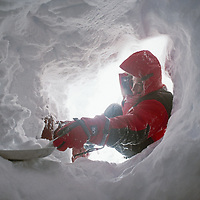 Cordillera Sarmiento, Patagonia, Chile. A mountaineer digs out a storm-choked entrance to a snow cave shelter.