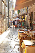 View along the Prijeko street with restaurants with outside seating shops and tourists in evening sunshine Dubrovnik, old city. Dalmatian Coast, Croatia, Europe.