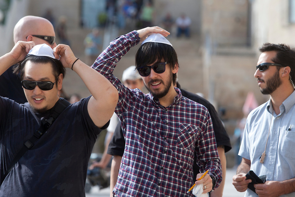 American band Linkin Park members Joseph Hahn (L), and Mike Shinoda (C) place skullcaps on their heads during a visit to the Western Wall, the holiest site to Judaism, in the Old City of Jerusalem, Israel, on November 15, 2010.