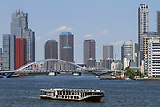 A pleasure boat on in front of St Luke's Tower (left) and tall apartment buildings around Tokyo Bay..Japan. Thursday May 30th 2019