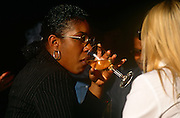 A woman of afro-Carribean parentage sits with friends sipping white wine from a glass in a London bar.