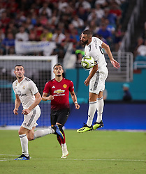 July 31, 2018 - Miami Gardens, Florida, USA - Real Madrid C.F. forward Karim Mostafa Benzema (9) leaps to pass the ball with a header, as Real Madrid C.F. forward Gareth Bale (11) (left) and Manchester United F.C. midfielder Andreas Pereira (15) (center) follow the action, during an International Champions Cup match between Real Madrid C.F. and Manchester United F.C. at the Hard Rock Stadium in Miami Gardens, Florida. Manchester United F.C. won the game 2-1. (Credit Image: © Mario Houben via ZUMA Wire)
