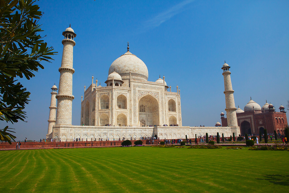 The Taj Mahal with vibrant blue sky and green grass. It is an ivory-white marble mausoleum on the southern bank of the river Yamuna.