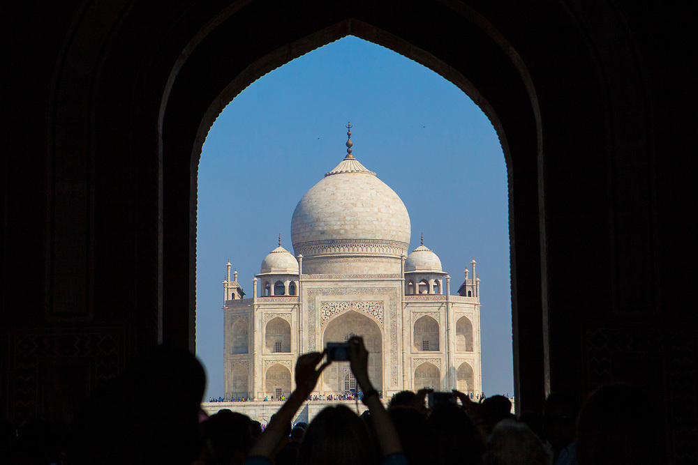 The Taj Mahal through an entrance arch with crowds in silhouette in the foreground and a tourist holding up a camera taking a photo