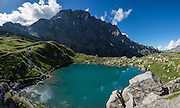 From Obersteinberg, don't miss the 2-3 hours round trip to the deep-blue tarn of Oberhornsee in the upper glacial basin, beneath snowcapped Grosshorn, Breithorn and Tschingelhorn. We loved hiking to the quiet retreat of Berghotel Obersteinberg, which offers tremendous views of waterfalls and peaks in Upper Lauterbrunnen Valley, in the canton of Bern, Switzerland, Europe. Lit by candle light at night, this romantic escape built in the 1880s recalls an earlier era without power. The main luxuries here are flush toilets down the hall, and traditional Swiss hot meals. The private double rooms lack electricity, and bowls of water serve as bath and sink. Obersteinberg is a 2-hour walk from Stechelberg, or 4 hours from Mürren, in one of the world's most spectacular glaciated valleys. The Swiss Alps Jungfrau-Aletsch region is honored as a UNESCO World Heritage Site. This image was stitched from multiple overlapping photos.