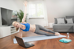 Young woman with laptop doing side plank pose on exercise mat in living room, Bavaria, Germany