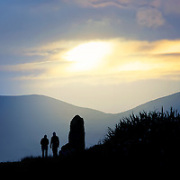 Standing Stones and two People during Sunset near Ballinskelligs, County Kerry, Ireland / bs042