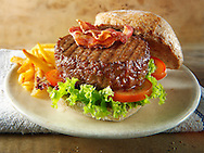 Beef burger with bacon in a wholemeal bun with salad and french fries photos. Funky Stock Photos