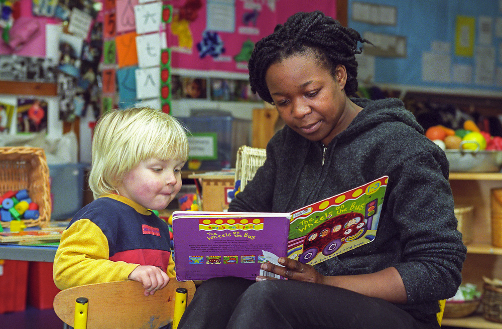Teacher reading a book with young child at a nursery school