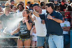 A cole slaw wrestler gets a quick wash during the coleslaw wrestling at the Cabbage Patch in New Smyrna Beach during Daytona Bike Week. FL, USA. March 12, 2014.  Photography ©2014 Michael Lichter.