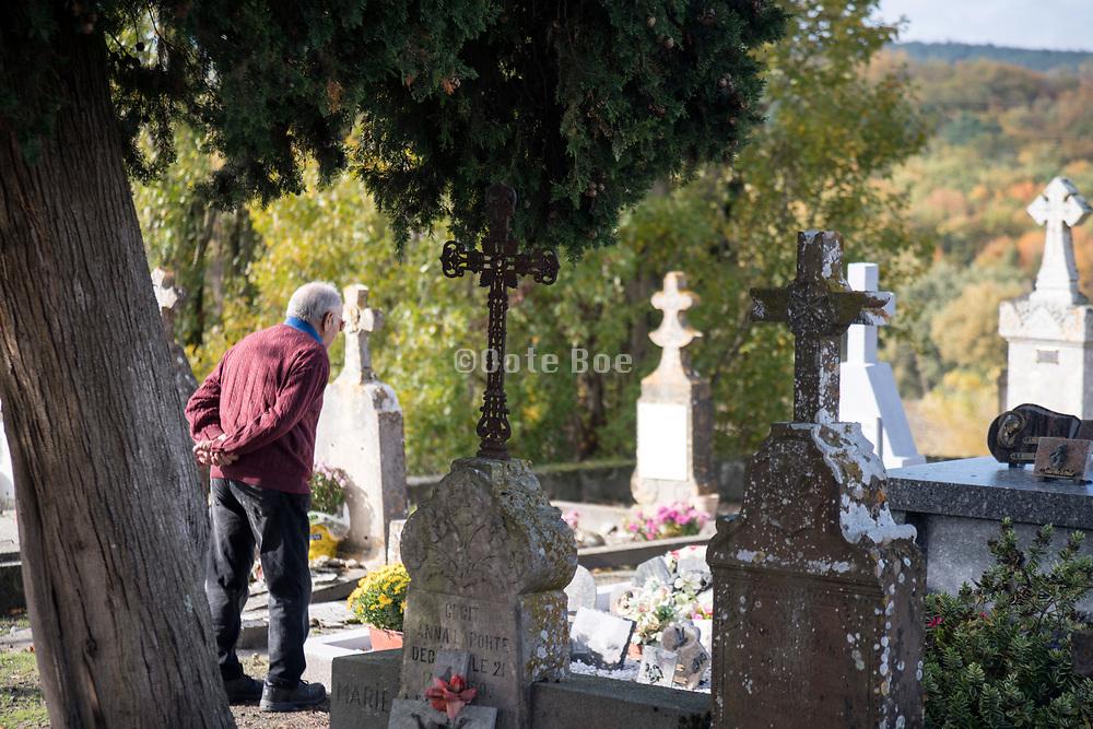 elderly man visiting graveyard