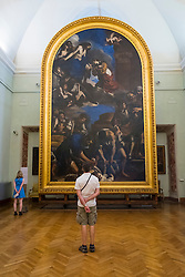 visitor looking at painting Guercino (Giovanni Francesco Barbieri) Seppellimento di Santa Petronilla (burial of Saint Petronilla) at  Museum Capitolini Rome, Italy